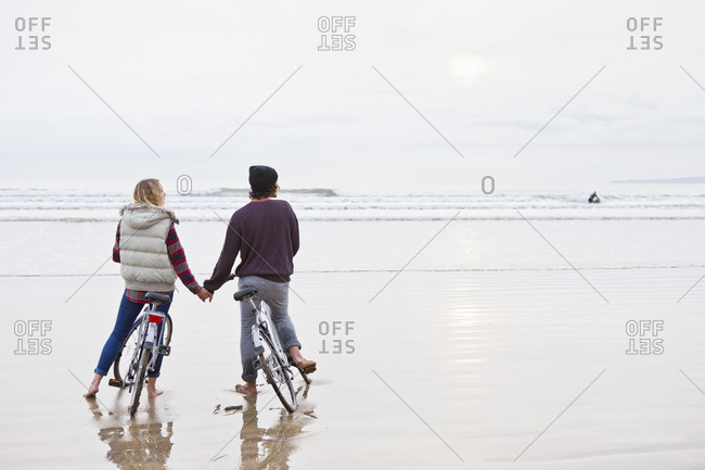 Couple with bicycles holding hands looking at ocean view from beach