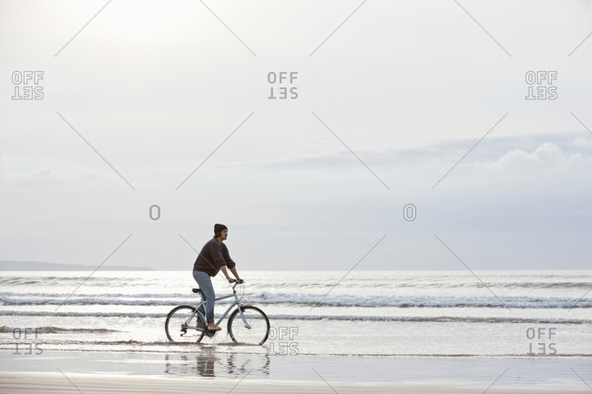 Man riding bicycle in ocean surf