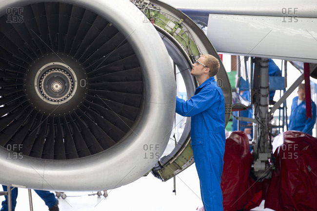 Aircraft maintenance technician safety checking airplane engine in airport hangar