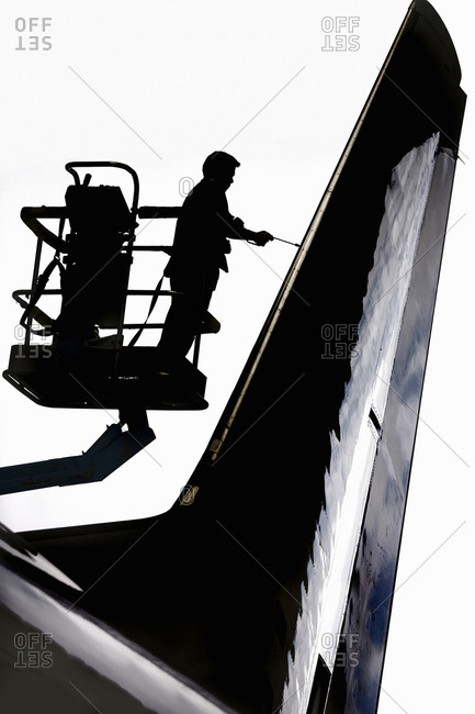 Aero Engineer Working On Tail Of Aircraft In Hangar