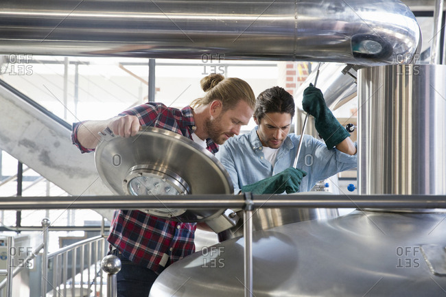 Brewery Workers Checking Fermentation Process In Steel Vat