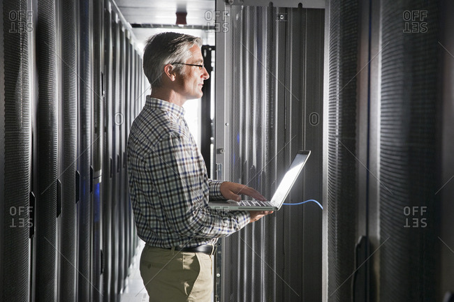 Service Technician With Laptop Working In Secure Data Centre