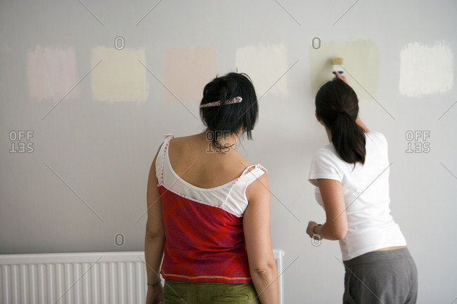 Two women decorating at home, testing different paint colors on wall, rear view