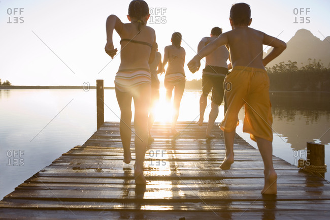 Family, in swimwear, running along jetty, jumping into lake at sunset, rear view (lens flare)
