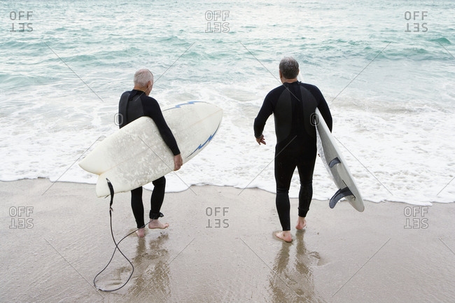 Male surfers in wetsuits on beach, walking into surf, rear view