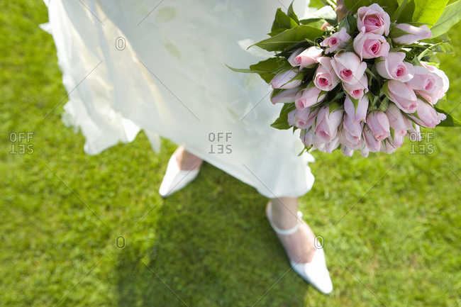 Bride with bouquet of flowers, low section, elevated view