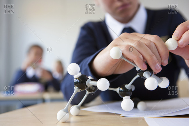 Close up of student in school uniform assembling atom model at desk in classroom