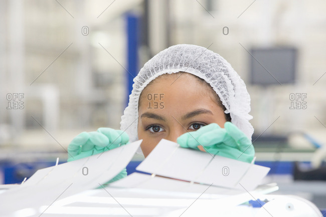 Technician worker arranging solar cells to form solar panel on production line