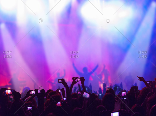 Fans At Concert Enjoy Music And Take Photos On Cellphones