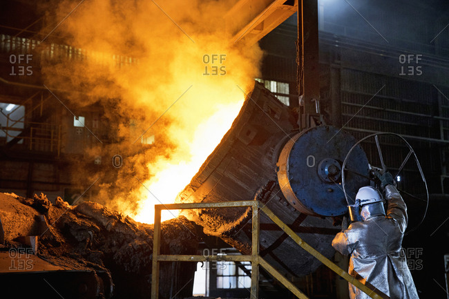 Worker In Protective Clothing Pouring Molten Metal In Foundry