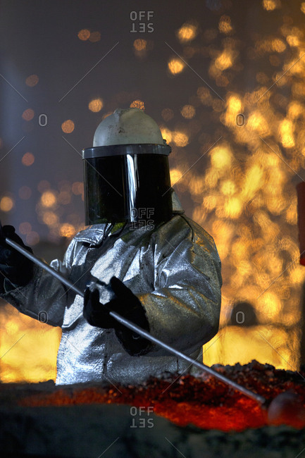 Worker In Protective Clothing Checking Molten Metal In Foundry