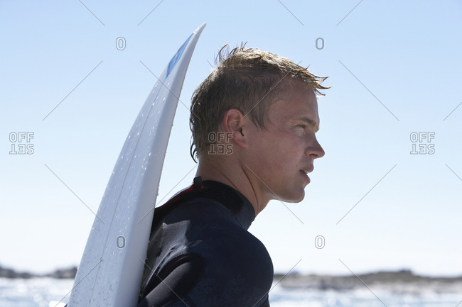 Young man in wetsuit standing on beach with surfboard, close-up, profile
