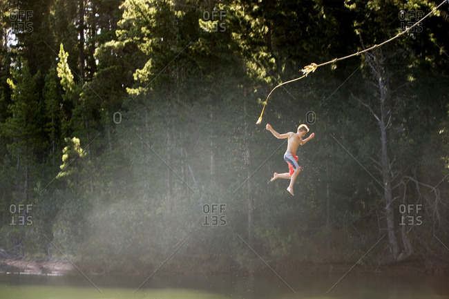 Boy (9-11), in swimming shorts, letting go of rope swing above lake, side view