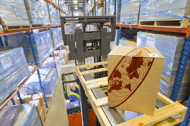 Warehouse worker moving cardboard box on forklift