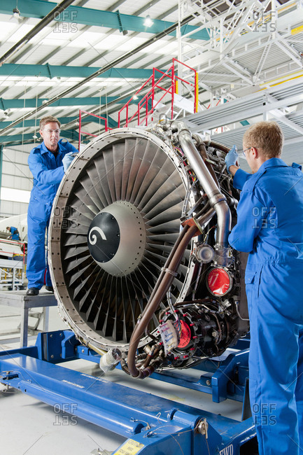 Engineers repairing engine of passenger jet in hangar