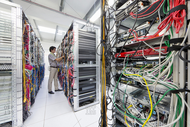 Technician checking cables in Server room of data center