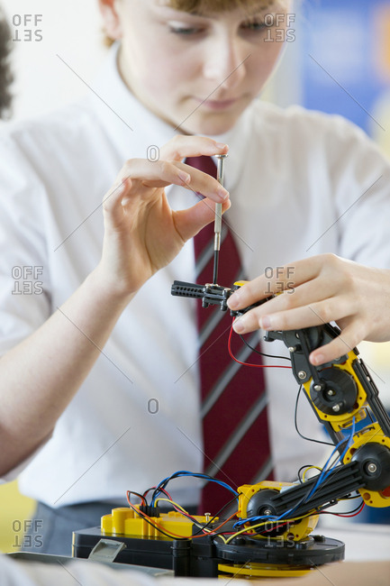 Close up focused high school student assembling robot in science class