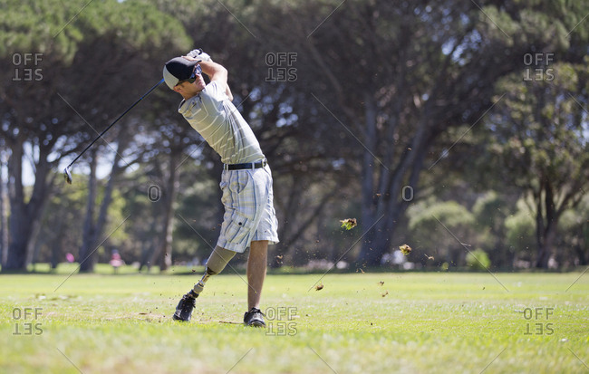 Male Golfer With Artificial Leg Teeing Off On Golf Course