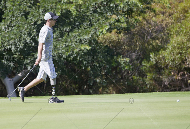 Male Golfer With Artificial Leg On Course Putting Ball On Green