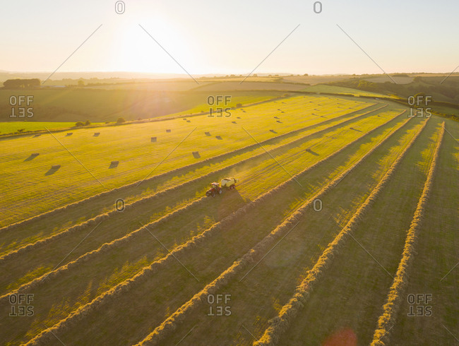 Aerial View Of Tractor Baling Hay In Field At Sunset