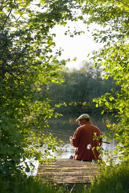 Fisherman fishing with rod on idyllic lake dock
