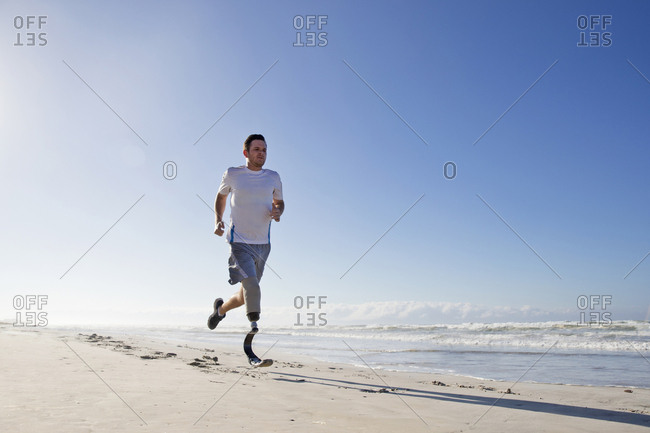 Man With Blade Style Artificial Leg Running Along Beach