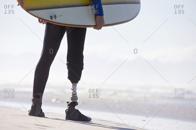 Close Up Of Surfer With Artificial Leg Standing On Beach