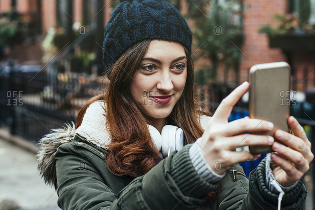 Smiling young woman in warm clothing taking selfie on smart phone in city