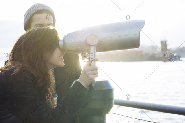 Smiling woman looking through coin operated binoculars by man in city