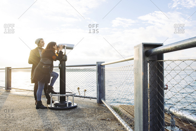 Young woman looking through binoculars while standing by man at observation point