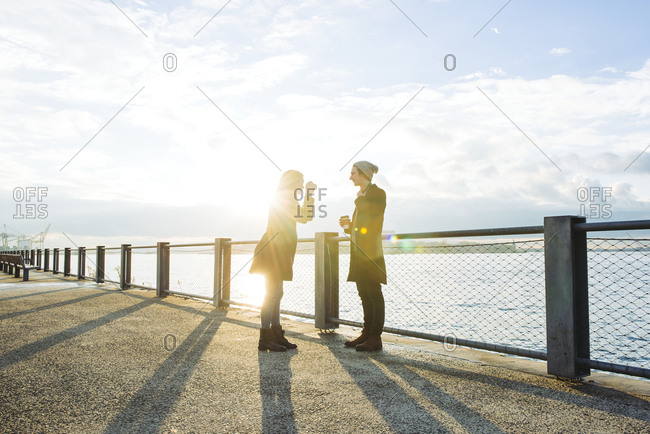 Young woman photographing man on promenade against sky during sunset