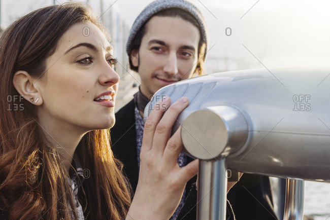 Young couple looking through coin operated binoculars