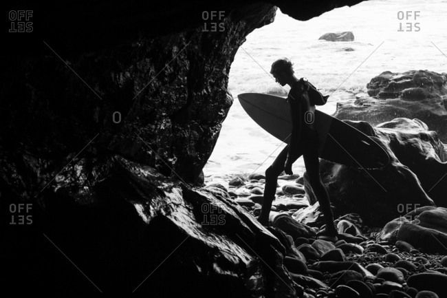 Tofino, Vancouver Island, BC, Canada - January 25, 2015: Surfer carrying board through cave by ocean