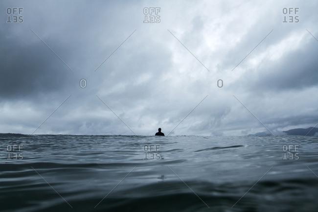 Person in wetsuit standing in the ocean