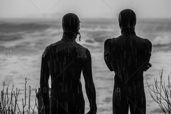Rear view of surfers in wetsuits watching a rain storm