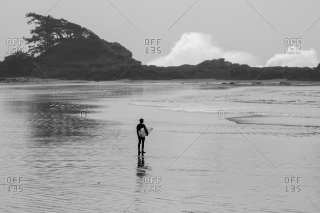 Surfer standing in shallow water watching waves