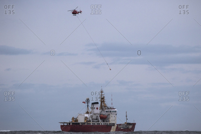 Canadian icebreaker ship and helicopter in the ocean