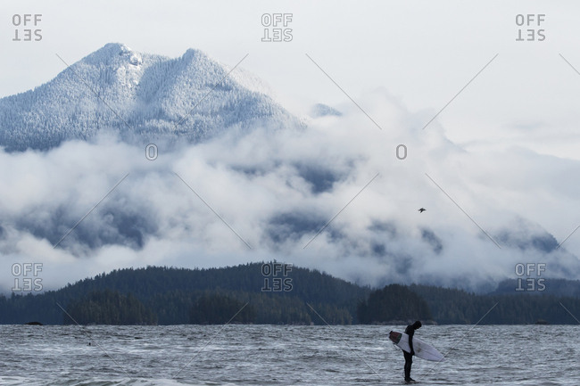 Tofino, Vancouver Island, BC, Canada - March 15, 2016: Surfer standing on rock in the ocean by large mountain