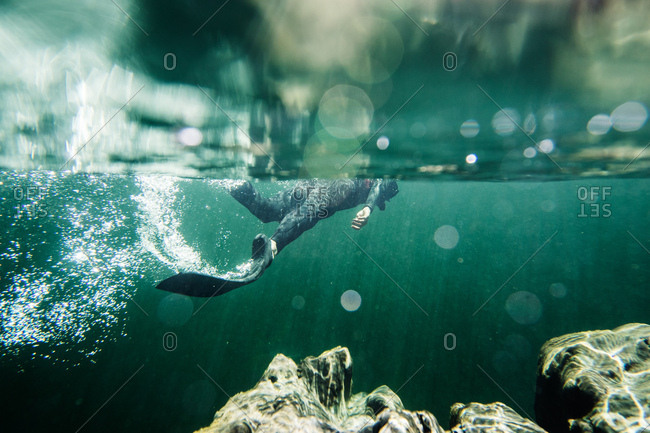 Underwater view of diver wearing flippers swimming in the ocean