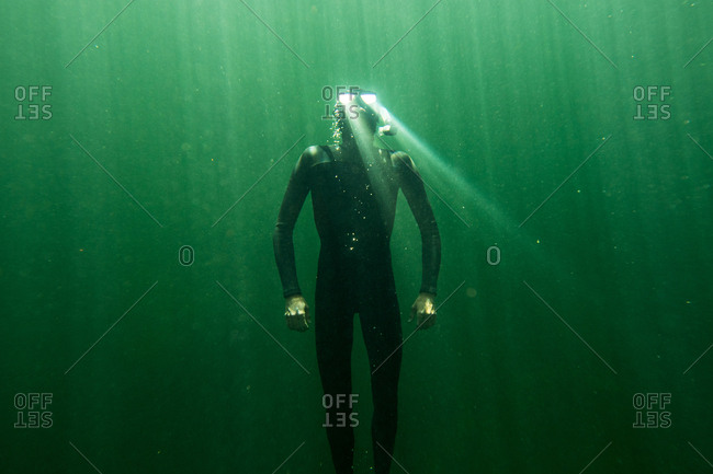 Underwater view of diver with light reflecting off of his goggles