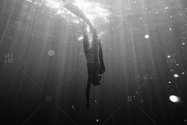 View of scuba diver swimming down underwater
