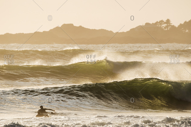 Surfers paddling on boards as waves build