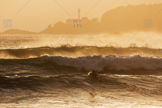 Surfer paddling on board as waves build at sunset