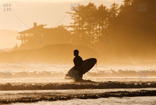 Tofino, Vancouver Island, BC, Canada - June 3, 2016: Surfer carrying board while walking in waves at sunset