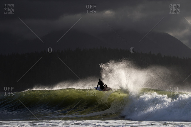 Surfer riding a wave under stormy skies