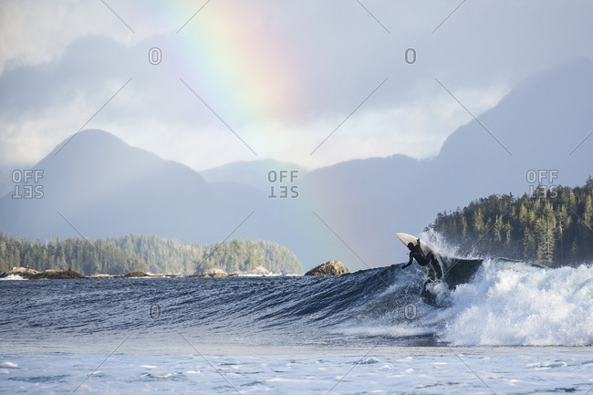 Surfer riding a wave under a rainbow in the sky