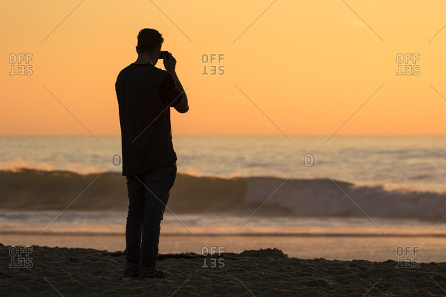 Man silhouetted photographing ocean waves