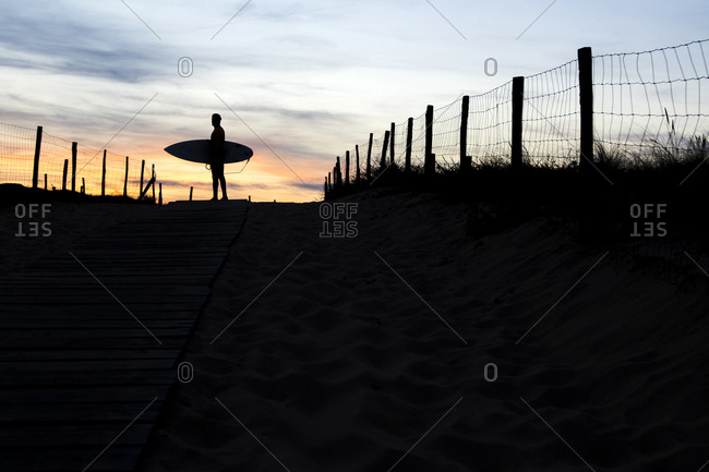 Surfer silhouetted in coastal setting