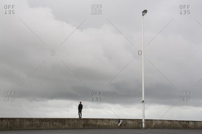Man on a coastal wall