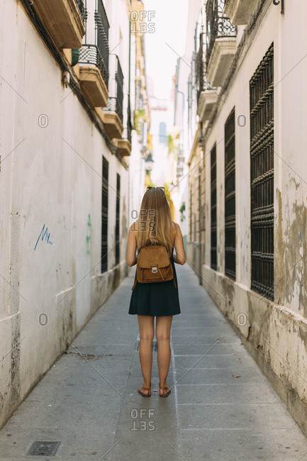 Young woman wearing backpack and skirt standing in narrow alleyway between buildings